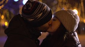 Man hugging and kissing girlfriend at night stock footage