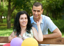 Happy romantic couple with balloon sit on bench in city park and posing, summer season, adult people man and woman Stock Image