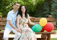 Happy romantic couple with balloon sit on bench in city park and posing, summer season, adult people man and woman Royalty Free Stock Image