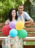 Happy romantic couple with balloon sit on bench in city park and posing, summer season, adult people man and woman Royalty Free Stock Images