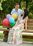 Happy romantic couple with balloon sit on bench in city park and posing, summer season, adult people man and woman Royalty Free Stock Photography