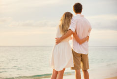 Happy romantic couple on the beach at sunset Stock Photos