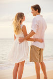 Happy romantic couple on the beach at sunset Stock Images