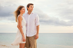 Happy romantic couple on the beach at sunset embracing each other Stock Images