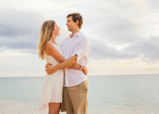 Happy romantic couple on the beach at sunset embracing each other Royalty Free Stock Photo