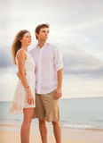 Happy romantic couple on the beach at sunset embracing each other Royalty Free Stock Images