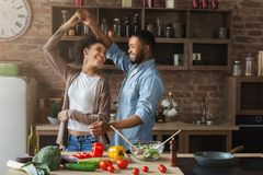 Happy romantic couple dancing in kitchen while cooking. Together royalty free stock image