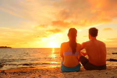Happy Romantic Couple Enjoying Sunset at Beach. Happy Romantic Couple Enjoying Beautiful Sunset at the Beach Sitting in Sand looking at ocean sea and colorful Stock Image