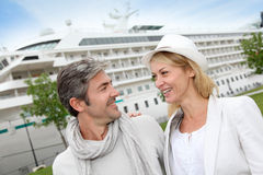 Happy romantic couple going on a cruise. Happy romantic couple standing in front of cruise boat Royalty Free Stock Images
