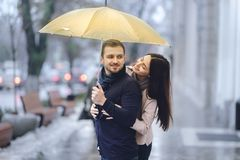 Happy romantic couple, guy and his girlfriend dressed in casual clothes are hugging under the umbrella and look at each royalty free stock photography