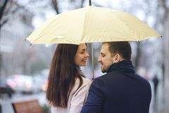 Happy romantic couple, guy and his girlfriend dressed in casual clothes walk under the umbrella and look at each other stock images