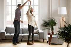 Happy romantic couple dancing in living room at home together. Happy romantic couple having fun in new home, men holding womans hand up leading in dance enjoying royalty free stock images