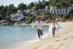 Happy enjoying guy run on the beach in Greece, romantic escape, lifestyle,  on a beautiful seascape background. royalty free stock photos