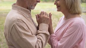 Happy romantic couple holding hands during outdoor date, grandparents love. Stock footage stock video
