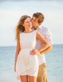 Happy romantic couple kissing on the beach at sunset Stock Photography