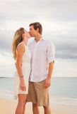 Happy romantic couple kissing on the beach at sunset Royalty Free Stock Images
