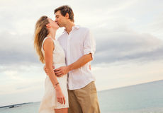 Happy romantic couple kissing on the beach at sunset Royalty Free Stock Photo