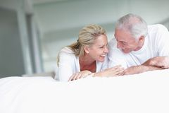 Happy romantic couple lying in bed Stock Image