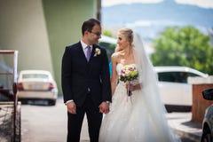 Happy romantic couple of newlyweds holding hands Stock Photo