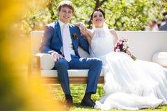 Happy, romantic couple of newlyweds posing on white sofa Stock Photos