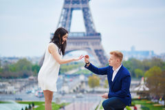 Happy romantic couple in Paris. Romantic engagement in Paris, men proposing to his beautiful girlfriend near the Eiffel tower. Surprise proposal or elopement Royalty Free Stock Photos