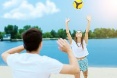 Happy romantic couple playing with soccer ball in summer royalty free stock images