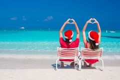 Happy romantic couple in red Santa Hats at beach Stock Photography