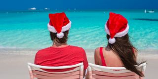 Happy romantic couple in red Santa Hats at Stock Image