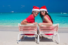 Happy romantic couple in red Santa Hats at Royalty Free Stock Photos