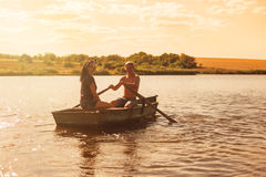 Happy romantic couple rowing a boat Stock Photography