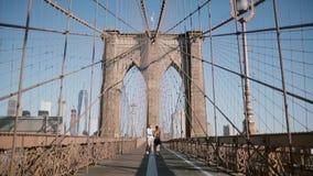 Happy romantic couple run forward along Brooklyn Bridge in New York City, hold hands on a beautiful sunny summer day. Happy romantic couple run forward along stock video