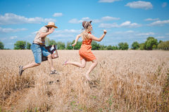 Happy romantic couple running with old suitcase in Stock Image