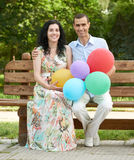 Happy romantic couple sit on bench in city park and posing, summer season, adult people man and woman Stock Photos