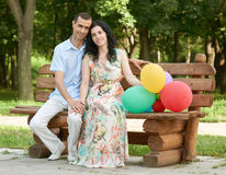 Happy romantic couple sit on bench in city park and posing, summer season, adult people man and woman Stock Photography
