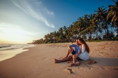 Happy romantic couple sitting on tropical beach on palm trees background, hugging each other and enjoy sunset. Vacation royalty free stock photo