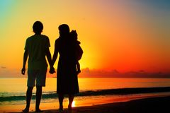 Happy romantic couple with small child on tropical beach. Happy romantic couple with small child on sunset tropical beach Royalty Free Stock Images