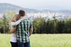 Happy romantic couple standing arm in arm stock photo