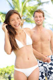Happy romantic couple summer vacation beach fun. Joyful multi-ethnic young couple laughing elated together on tropical beach holiday on resort. Mixed race Stock Photos