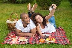 Happy romantic couple taking pictures on picnic Royalty Free Stock Photos