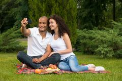 Happy romantic couple taking pictures on picnic Stock Images