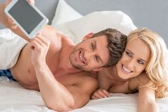 Happy Romantic Couple Taking Pictures Using Phone Royalty Free Stock Photography