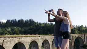 Happy romantic couple tourists in front of old bridge make photo. On sunny day stock video