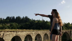 Happy romantic couple tourists in front of old bridge. On sunny day stock footage