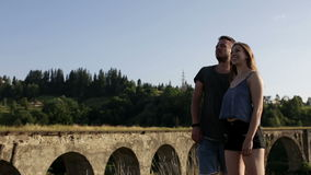 Happy romantic couple tourists in front of old bridge. On sunny day stock video footage