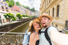 Happy romantic couple of tourists makes selfie self-portrait in Karlovy Vary while traveling across Europe. Happy romantic couple of tourists makes selfie self stock photography