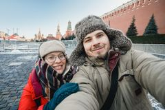 Happy romantic couple of tourists in warm clothes in winter makes a self-portrait selfie in front of the Kremlin on Red Square in stock photos