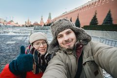 Happy romantic couple of tourists in the winter in warm clothes and hats makes self-portrait selfie in front of the Kremlin on Red stock image