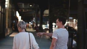 Happy romantic couple walk holding hands, turning left along evening Soho street, New York, enjoying evening city date. stock video