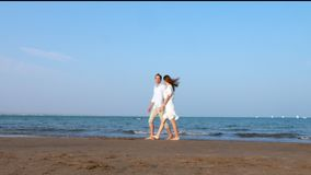 Happy romantic couple walking down the beach at sunset. Happy romantic couple walking down the sea beach at sunset stock video