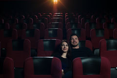 Happy romantic couple watching movie in theater. Royalty Free Stock Photography